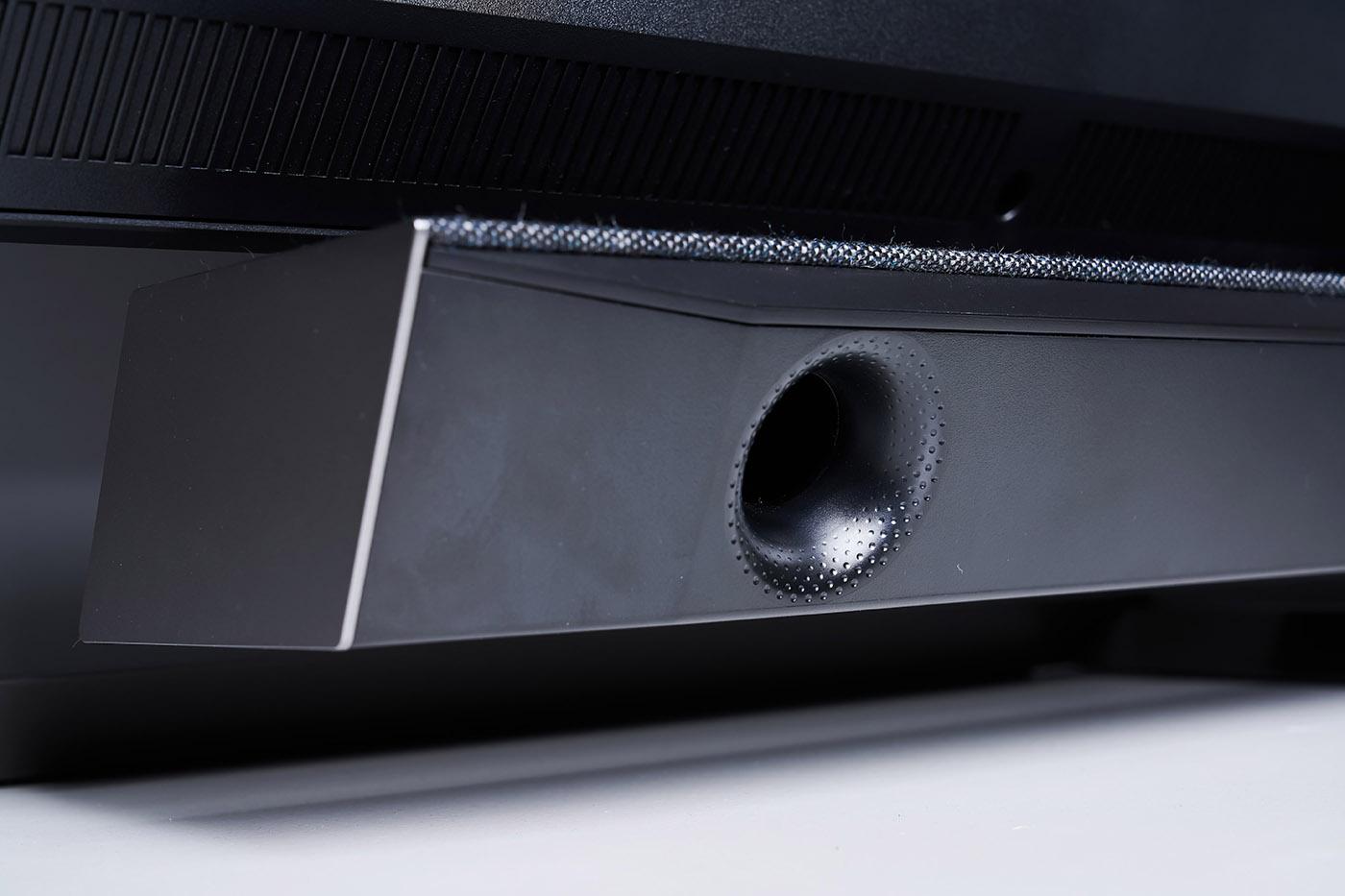 繼續檢視機體背面,則可注意到音響系統背部配置著低音反射孔,能強化音效低頻量感與延伸,而低音反射孔最外部採用凹凸圓點設計,則是為了避免低音駐波,且相信關注音響設備的人也應該發現,低音反射孔朝斜下方設計,透過向下輸出聲波的同時,也能利用放置顯示器的桌面與背牆反射擴散低音,創造更好的低頻表現。